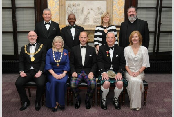 HRH the Earl of Forfar is pictured in a group of people wearing formal attire at the Merchants House